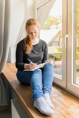 Girl sitting at the window and planning her life with notes