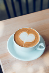 White mug of coffee with heart shaped latte art in sunlight on wooden table at coffee shop.  Vintage color, filter effect