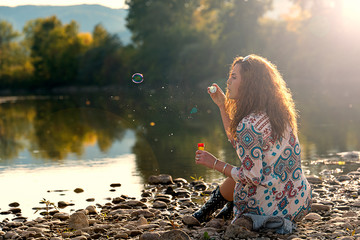 Beautiful girl makes bubbles of soap