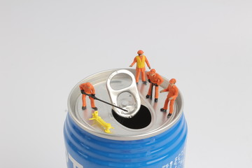 min worker on top of soda can