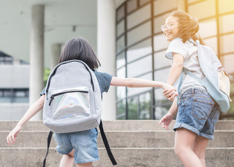 Back to school education concept with girl kids (elementary students) carrying big backpacks going to class holding hand in hand together, running and walking up school building stair happily