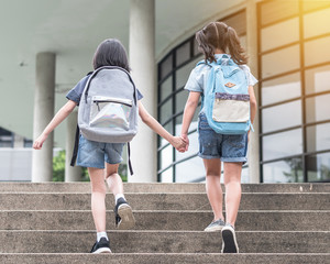 Back to school education concept with girl kids (elementary students) carrying backpacks going to class holding hand in hand together walking up school building stair happily