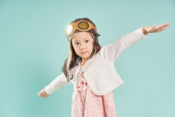 Little asian girl wear aviator glasses and enjoy her travel dreams , mint green background .