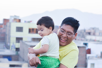 Happy latin family - daddy with his toddler son playing