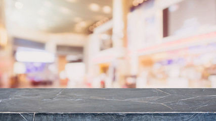 Black stone table top on blurred with bokeh shopping mall background - can be used for display or montage your products