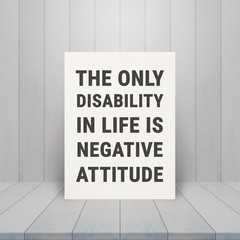 "Inspiration Quote "" THE ONLY DISABILITY IN LIFE IS NEGATIVE ATTITUDE"" on paper at wooden table top and wooden wall background"