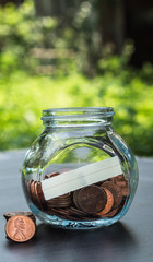 one cent coins in a glass jar on the table in a garden