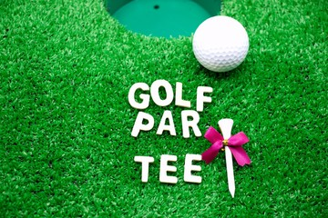 Golf party invitation with golf ball and wording are on green grass next to golf hole