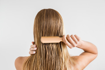 Woman with comb brushing her wet blonde hair after shower on the gray background. Cares about a healthy and clean hair. Beauty salon concept.