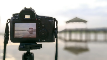 The camera is on a tripod, taking a photo of a pavilion in a pool or swamp or lake.