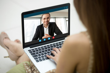 Young woman communicating with man in formal suit via video call application. Dressy couple chatting. Long distance relationship, virtual communication. Close up view over shoulder, focus on screen.