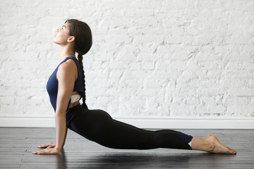 Young attractive woman practicing yoga, stretching in Urdhva mukha shvanasana exercise, upward facing dog pose, working out wearing sportswear black top and pants, indoor full length studio background