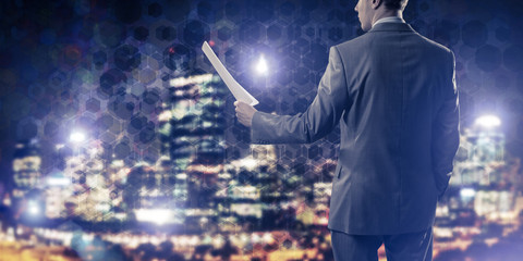 Rear view of businessman against night cityscape background and
