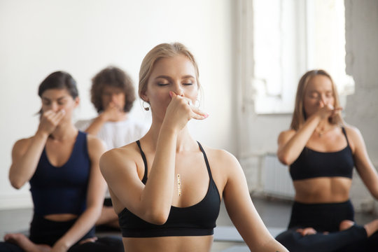 Group of young sporty people practicing yoga lesson with instructor, making Alternate Nostril Breathing, nadi shodhana pranayama exercise, sitting in Sukhasana pose, working out, indoor close up image