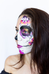 Sugar Skull Halloween Makeup.  Dia de los Muertos. Brunette girl with Mexican style Halloween face painting. Red rose, flower hair decor