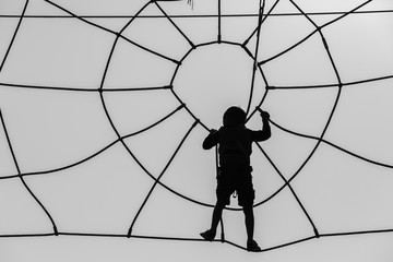 Boy silhouetted Climbing Spiderweb Cable Obstacle Course.
