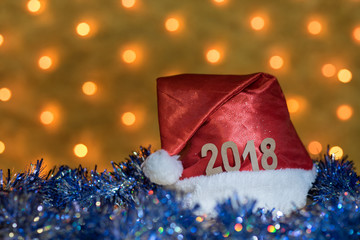 Red cap and blue tinsel with figures of 2018 on a table on the background of a New Year's garland with blurred golden lights