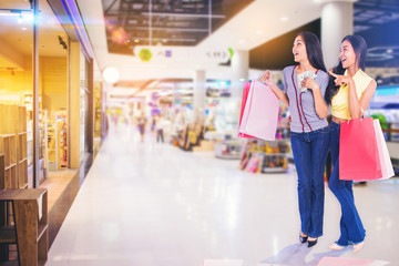 woman friends holding shopping bags money in hand excited to shopping in the shopping mall