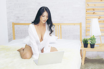 sexy asian young woman playing a laptop PC  in the morning  white bedroom