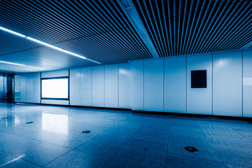 Blank billboard in metro station, blue tone.