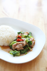 fried pork with Chinese Kale and rice on wood background , Thai food