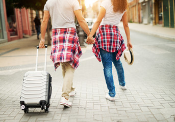 Rear view of young couple walking through the city with baggage.
