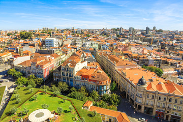 Panoramic views of historic city center of Porto in Portugal from top of Clerigos Tower, one of the landmarks and icon of Oporto. Urban aerial cityscape. Beautiful sunny day.