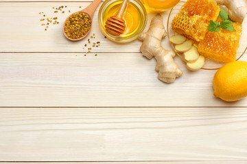 healthy background. honey, honeycomb, lemon, ginger on white wooden table. Top view with copy space