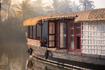 Fototapete - A traditional house boat is anchored on the shores of a fishing lake in Kerala's Backwaters.