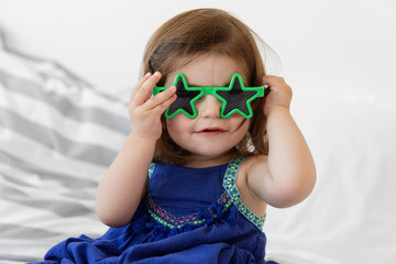 portrait of baby girl wearing star shaped glasses