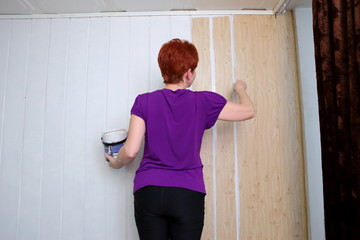 The woman is painting her apartment.
