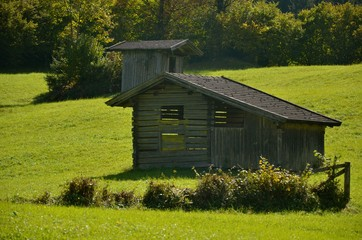 Two old wooden houses on the natural grass background.