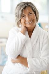 Portrait of smiling senior woman in bathrobe
