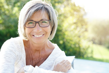 Cheerful mature woman with eyeglasses relaxing outside