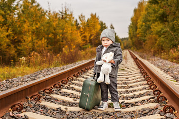 cute sad boy in retro clothes with a vintage green suitcase standing on rails in the forest