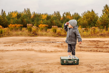 a boy in panties and a gray coat is standing on an old suitcase in the middle of a sandy country road, raising his hand to his forehead