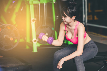 Young woman training with dumbbell in gym