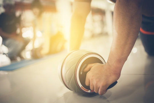 Man using abdominal roller for working out abdominals. Front view. Focus on hands.