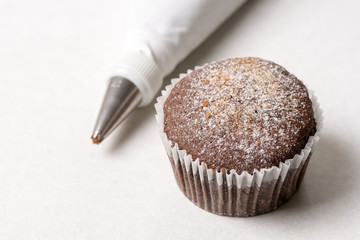 Chocolate cup cake with piping bag on the white marble background
