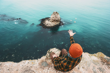 Man sitting on cliff above sea and throwing stones Travel Fashion Lifestyle orange hat and cozy shirt clothing harmony with nature authentic style concept