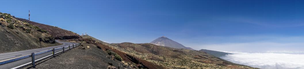 Bergstraße führt zum Teide-Observatorium auf Teneriffa als Panoramabild mit Vulkan Teide und Wolkenteppich im Hintergrund