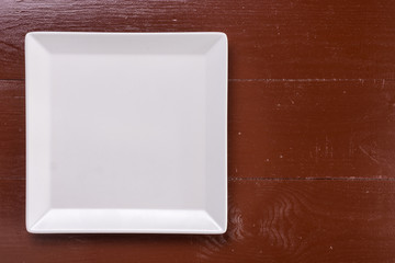 Flat lay above white square plate on the wooden brown board table