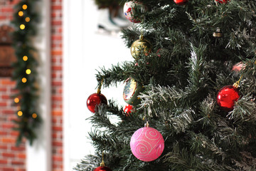 Multicolored Christmas tree toys hang on branches against the decorated door of the house