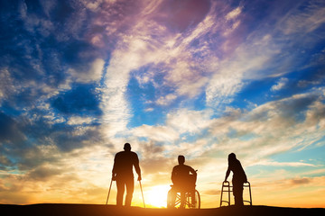 Three disabled people at the sunset.