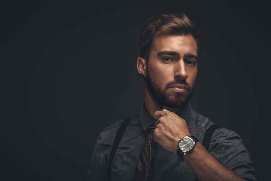 Handsome man combing beard