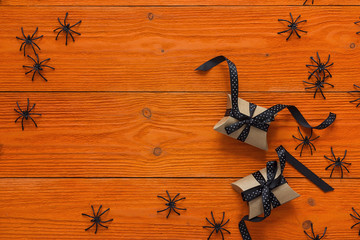 Decorative black spiders and gift boxes on orange wooden boards. Background for Halloween.