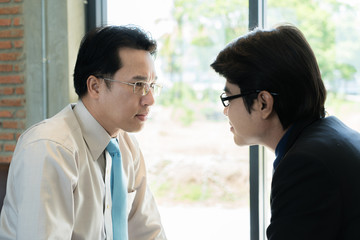 Asian two businessman looking at each other with tension. Rivalry business people at work. Business conflict between colleagues & office workers.