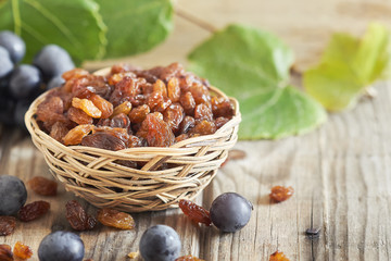 Raw raisins (dried grape) in woven basket. Copy space