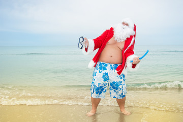Funny Santa claus in the sea. Christmas in the tropics.