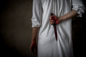Closeup Ghost woman holding knife hidden for kill with blood violence in house of ruin, nightmare, horror of scary fear on hell is monster devil in halloween festival, copy space the left. Wall mural